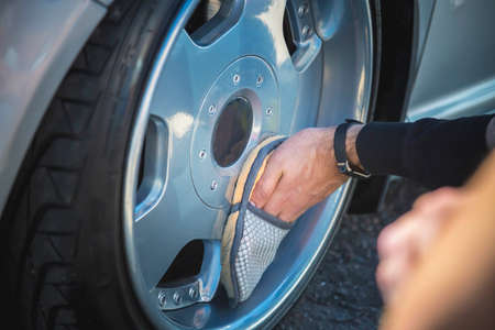 A man cleans the wheels of his car. Dropped silver car on air suspension. Фото со стока