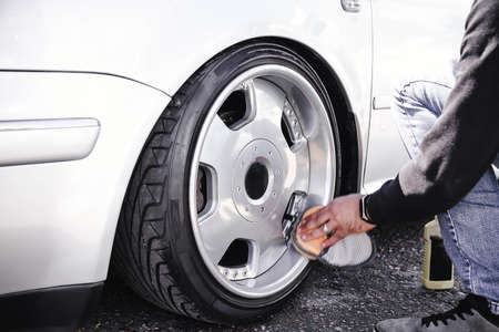 A man cleans and polishes the wheels of his car. Dropped white car on air suspension.