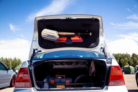 Open the trunk of a silver car that stands on the street. In the trunk of a shovel, baseball bat and warning triangle.