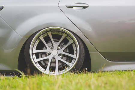 tuned alloy wheels with a wide rim on an lowered silver car standing on the grass.