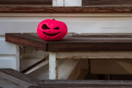 A pumpkin symbol of halloween, bright pink, stands on wooden steps. painted. Stock Photo