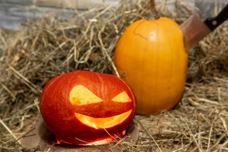 Two halloween pumpkins lie on a hay against the background of a stone wall. The knife is stuck in a yellow pumpkin. Light inside of jack-o-lantern Stock Photo
