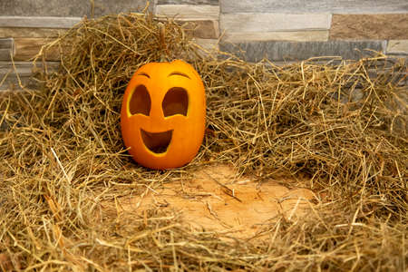 Yellow and happy smiling pumpkin. Halloween symbol on a gray stone wall background, stands on a hay and a wooden stand. Jack o lantern and copy space