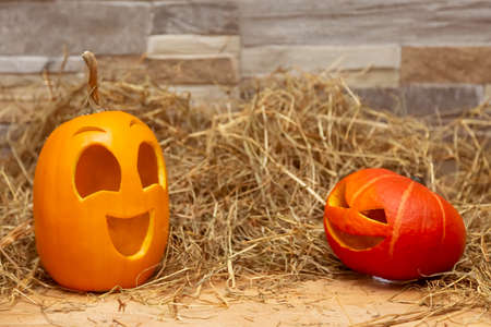 Two festive Halloween pumpkins stand next to each other and talk. Red and yellow jack o lantern