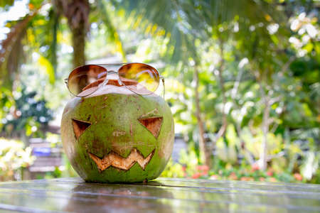 Fresh green coconut in a shape of halloween pumpkin. coconut with a face carved on it is on the table Stock Photo