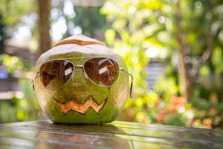 Fresh green coconut with sunglasses in a shape of halloween pumpkin. coconut with a face carved on it lying is on the table