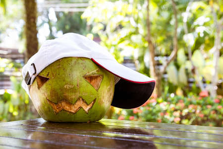 Fresh green coconut on the table. He is wearing a white baseball cap. Halloween symbols are carved on it. The face of a pumpkin.