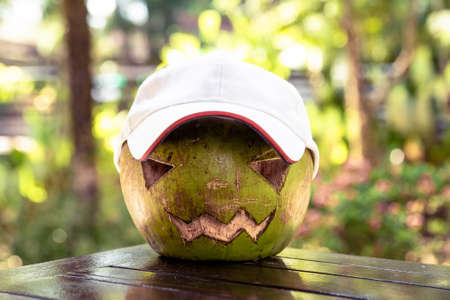 Fresh green coconut on the table. He is wearing a white baseball cap. Halloween symbols are carved on it. The face of a pumpkin. Green background Stock Photo