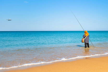 Woman fishing standing in the water near the shore. The sky is dropping the plane. Sunny clear morning on a tropical beach.
