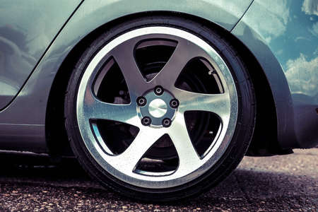 Alloy wheels of a sports car. Polished to shine. On a gray car. Closeup Фото со стока