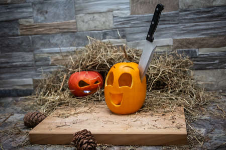 Two halloween pumpkins lie on a hay against the background of a stone wall. The knife is stuck in a yellow pumpkin Near the cones Stock Photo