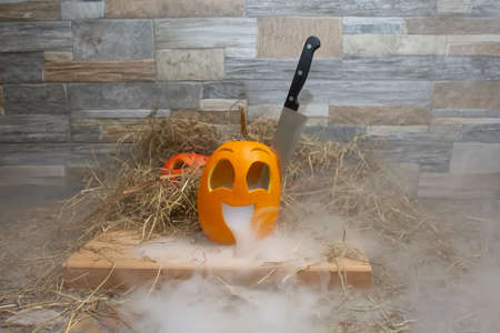 Yellow and funny halloween pumpkin with a knife in his head and smoke or steam from his mouth. Stands on a wooden stand against a stone wall. Red head at background Stok Fotoğraf