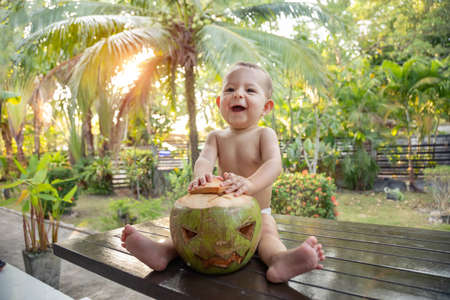 A one year old infant baby sits on a table against the background of palm trees and plays with a green coconut which is a symbol of Halloween in a tropical resort. Stock Photo