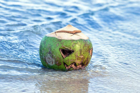 Fresh green coconut with a face carved on it like on a lantern jack in the water on the beach. Close up. Tropical halloween symbol. Holiday Vacation Concept