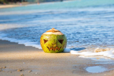 Green coconut with a face carved on it, like a halloween pumpkin. Lies in the sand on a tropical beach on a background of waves. Jack o lantern hut Stock Photo
