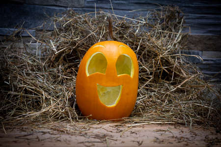 Yellow and happy smiling pumpkin. Halloween symbol on a gray stone wall background, stands on a hay and a wooden stand. Jack o lantern Imagens
