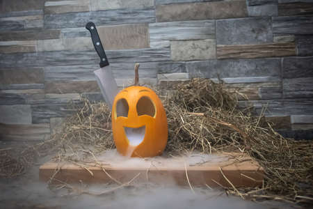 Yellow and funny halloween pumpkin with a knife in his head and smoke or steam from his mouth. Stands on a wooden stand against a stone wall