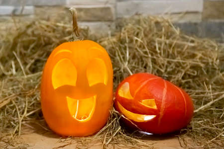 Two happy festive Halloween pumpkins stand next to each other and talk. Red and yellow jack o lanterns against of stone wall