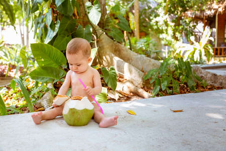 Pensive and passionate infant baby sits on the ground and eats and drinks green young coconut with spoon