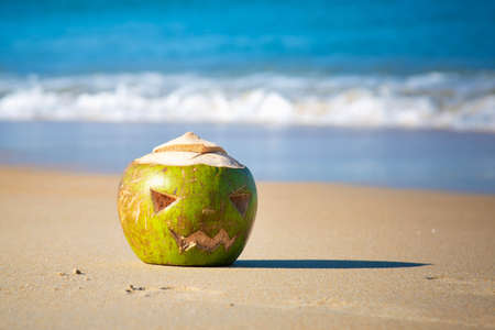 Halloween theme carved coconut. Lies in the sand on a tropical beach on a background of waves. Holiday trip concept