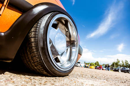 Mirror polished tuned wheels mounted on an understated orange car. Exclusive forged wheels on the pavement against the blue sky.