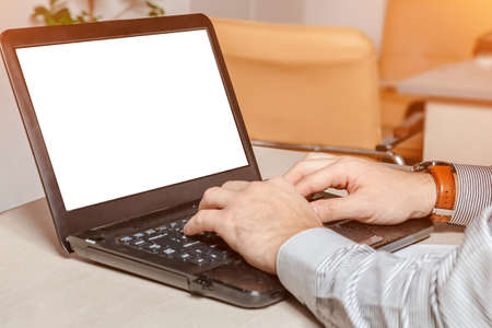 A man types on the keyboard in the office. Empty screen mockup