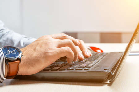 A man types on the keyboard in office. Hands and fingers on buttons close up Stock Photo
