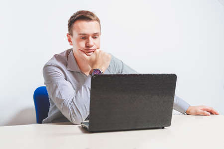 Matte toned image. young businessman working on laptop in office, being concerned