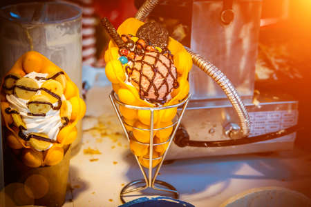 Two desserts, ice cream with banana and cookies on the table. Hong Kong Waffle. On the table. Stock Photo - 130483986