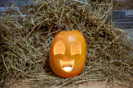 Yellow and happy smiling pumpkin. Halloween symbol on a gray stone wall background, stands on a hay and a wooden stand. Jack o lantern with lighting from the inside