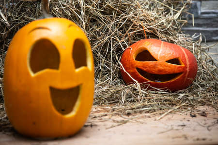 Two halloween pumpkins lie on the hay against the background of a gray stone wall. red at background in focus, yellow blurred in foreground Stock Photo