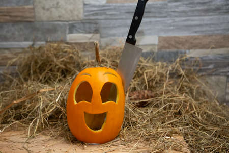 Yellow halloween pumpkin Jack-o-lantern lie on a hay against the background of a stone wall. The knife is stuck on it