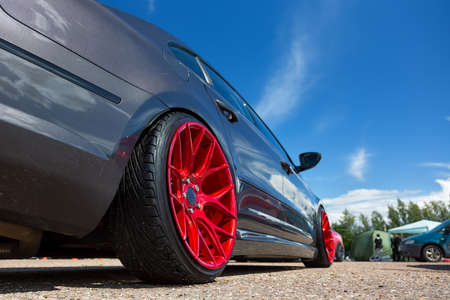 Gray car with lowered suspension and bright red forged wheels is on the parking. Against blue sky Stock Photo - 131723919