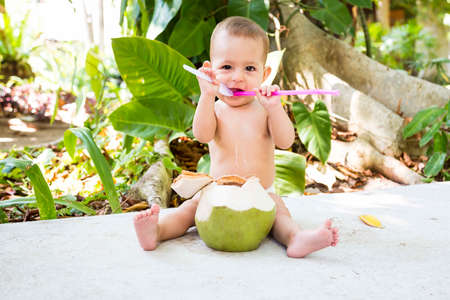 Happy infant baby at tropical vacation. Eats and drinks green young coconut. Sits on a ground and green forest forest on the background