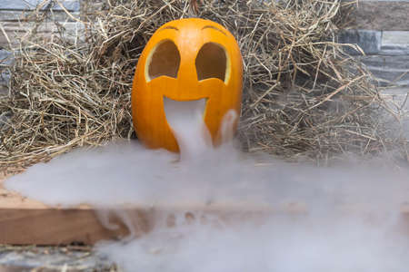 Yellow and very funny happy pumpkin for halloween celebration with a lot of smoke or vapor from the mouth. Stands on a wooden stand against a stone wall.