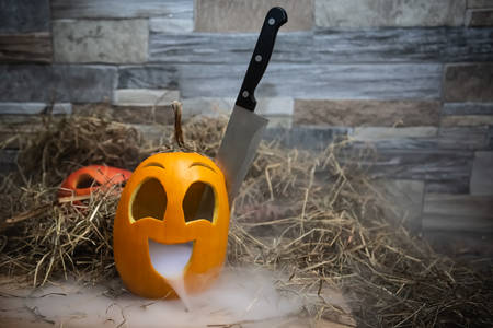 Yellow and funny halloween pumpkin with a knife in his head and smoke or steam from his mouth. Stands on a wooden stand against a stone wall. Red jack o lantern on background Stok Fotoğraf