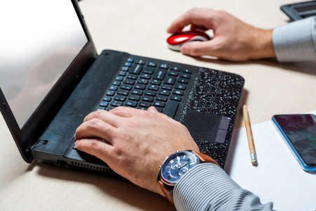 A man in the office typing on a laptop keyboard. Businessman at work. Hands close up
