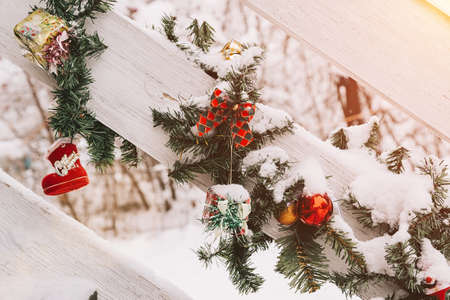 Christmas and New Year decorations on the street. On wooden handrails. Christmas tree and balls, toys, bows and small gifts. In the snow.