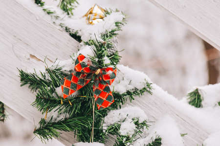 Christmas and New Year decorations on the street in the snow. Christmas tree branches and red festive bow Stock Photo
