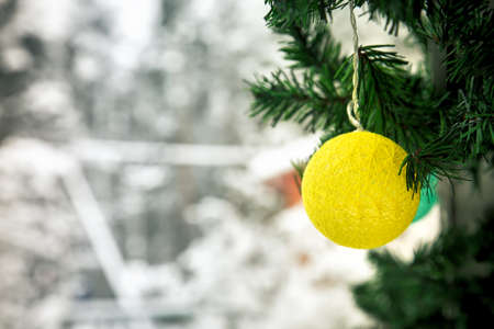 Christmas and New Year decorations on the street in the snow. A yellow ball of garland in the form of a ball of thread hangs on a Christmas tree. Place for text on the left.