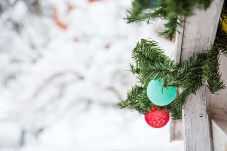 Christmas and New Year decorations on the street in the snow. A mint and red balls of garland in the form of a ball of thread hangs on a Christmas tree. Place for text on the left.