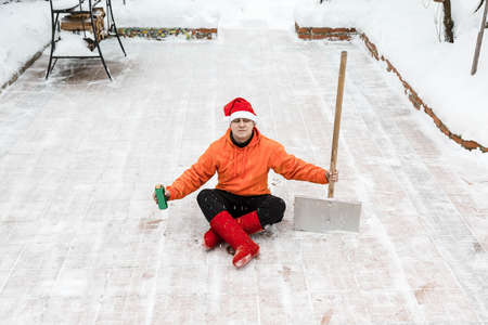 Man in a red Christmas hat and red winter boots in an orange sweater is sitting in a lotus position on the site of his yard with a shovel. He removed the snow from yard and rests. In the hand is a can