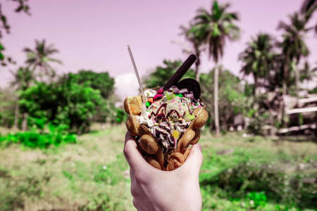 Toned with green and pink. Hong Kong waffle dessert in hand. Sweets with ice cream, cookies, syrup and sweets. Against the background of tropical vegetation. Tinted image