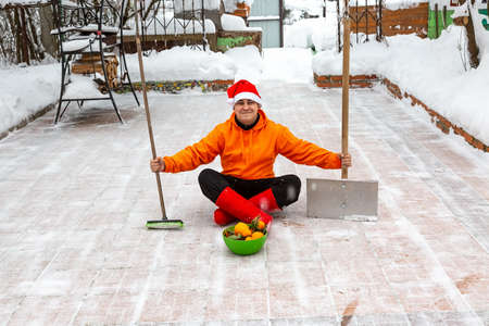 A man in a red New Year hat and orange jacket sits on the site of his yard with a brush and a shovel. He cleaned the snow from the backyard and was pleased with it. Nearby is a plate with tangerines.