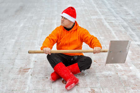 A man with a shovel for cleaning snow. Ready to fight the snow. Cleaned the territory. Sits in lotus position in a New Years hat and red felt boots. Look at side