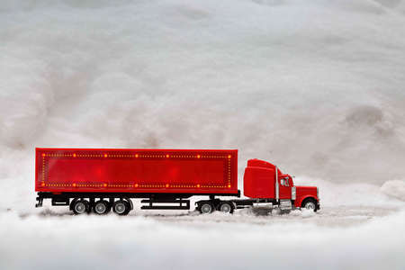 Festive truck in red. toy car rides on the background of real snowdrifts. Winter. Christmas holidays. Banco de Imagens