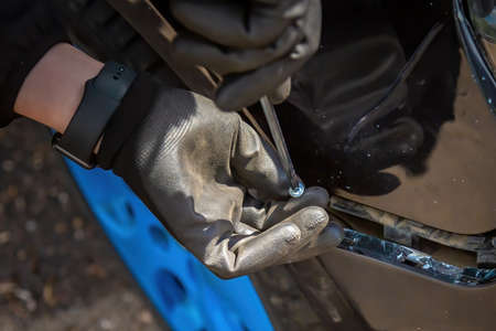 A man is trying to fix a car bumper. Screws in a screwdriver for fastening. Close-up of a hand in a black glove.