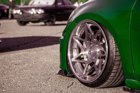 Exclusive tuned forged wheels mounted on a custom car pulled into a green vinyl film. Low car with air suspension. Фото со стока