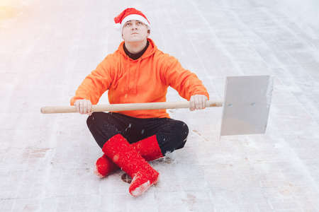 A man with a shovel for cleaning snow. Ready to fight the snow. Cleaned the territory. Sits in lotus position in a New Year's hat and red felt boots. Looking up