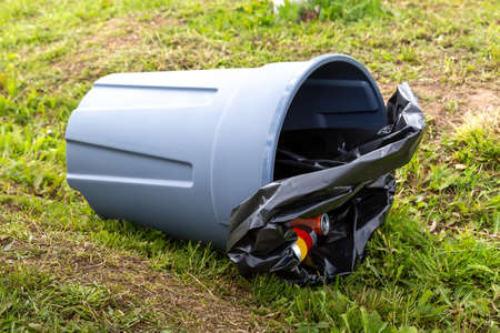 An overturned trash can is lying on the green grass.